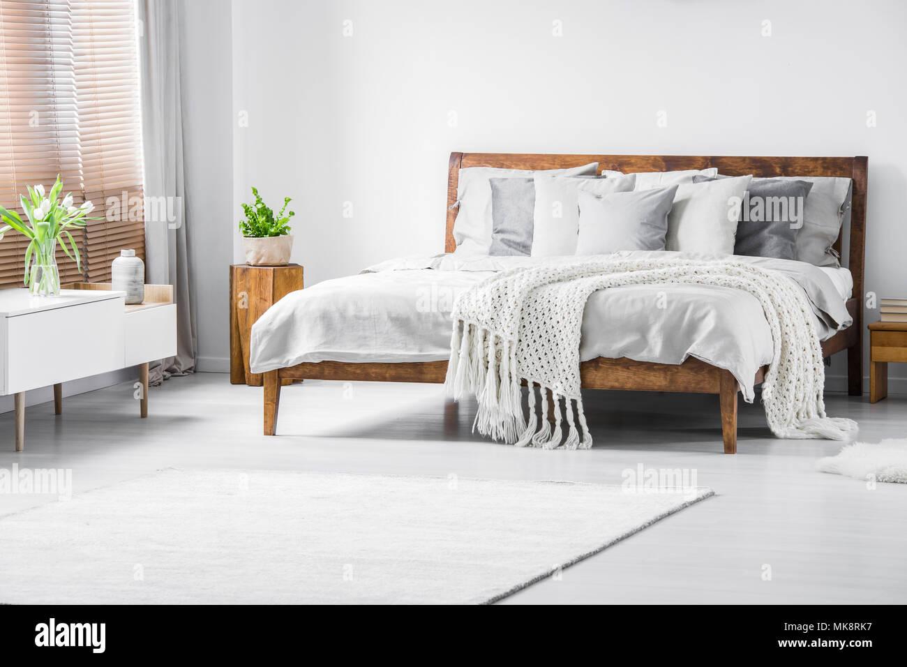 Weiß gestrickte Decke auf Bett aus Holz im minimal Schlafzimmer ...