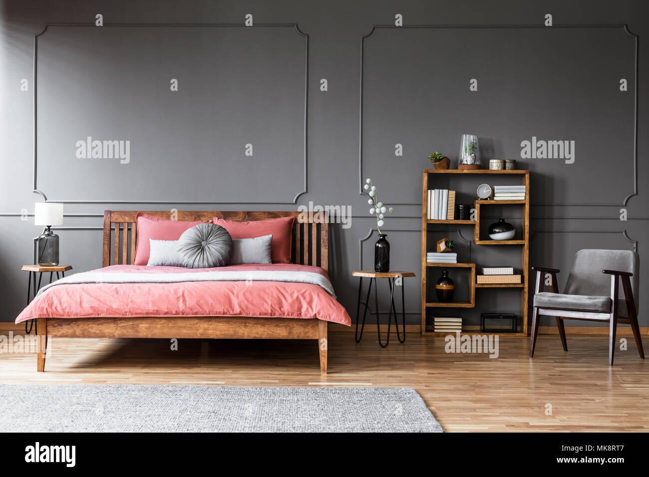 Bett aus Holz mit rosa Bettwäsche gegen graue Wand mit Spritzguss in ...