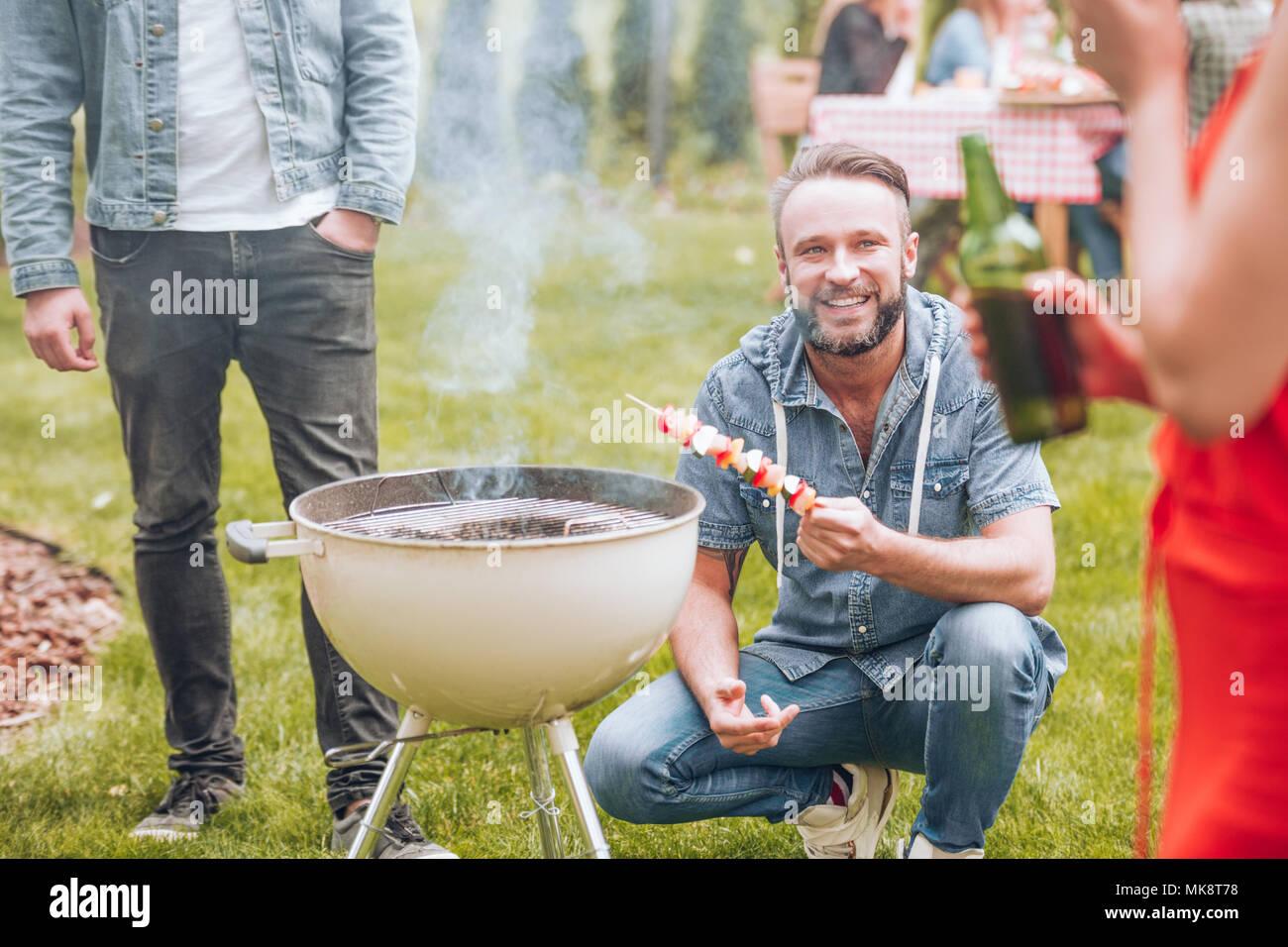 Glückliche Menschen grillen ein schaschlik während einer Gartenparty im Sommer Stockbild