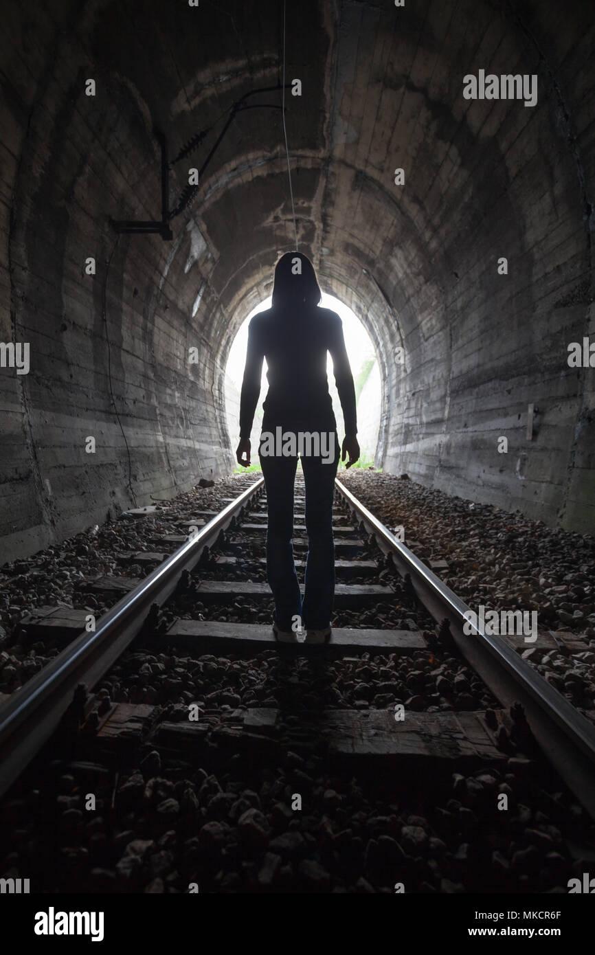 Mann Silhouette, die in einem Tunnel in der Mitte der Gleise mit Blick auf das Licht am Ende des Tunnels in einem konzeptionellen Bild Stockbild