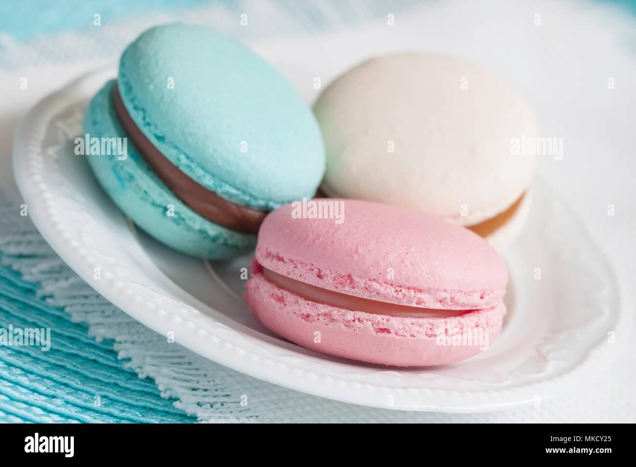 Drei Makronen in verschiedenen Farben und unterschiedlichen Geschmack in eine weiße Platte Stockbild