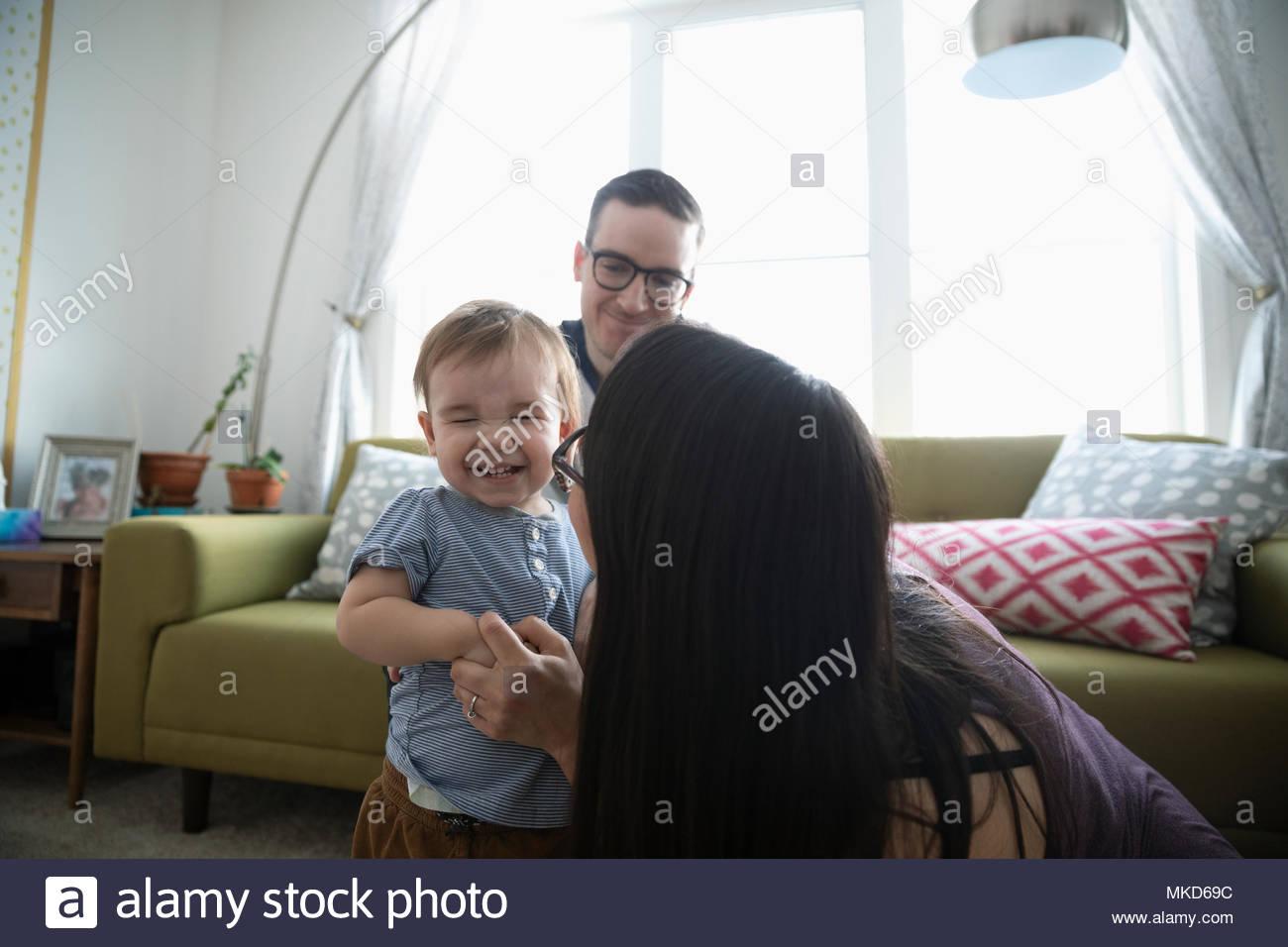 Liebevolle Eltern spielen mit lachendes Baby Sohn im Wohnzimmer Stockbild