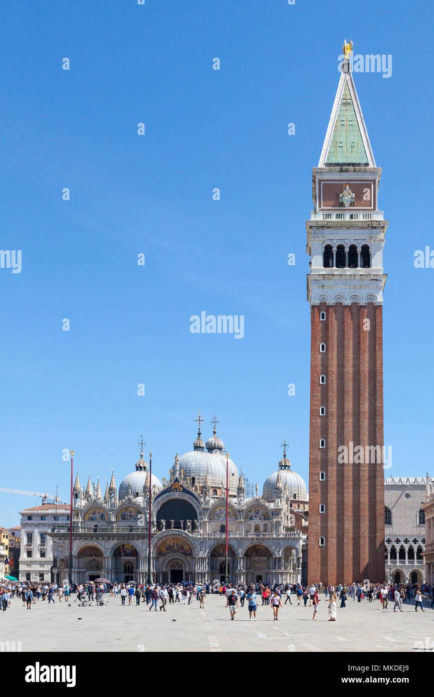 Touristen Sightseeing in Piazza San Marco (Markusplatz), Venedig, Venetien, Italien vor St Marks Kathedrale (Basilca San Marco) und der Campanile Stockbild