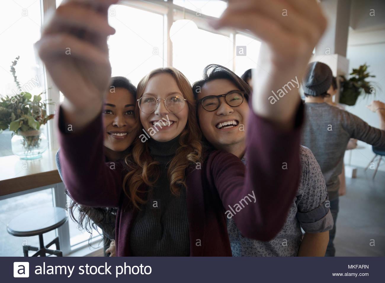 Lächelnd, begeisterte junge Freunde unter selfie mit Kamera Handy Stockbild
