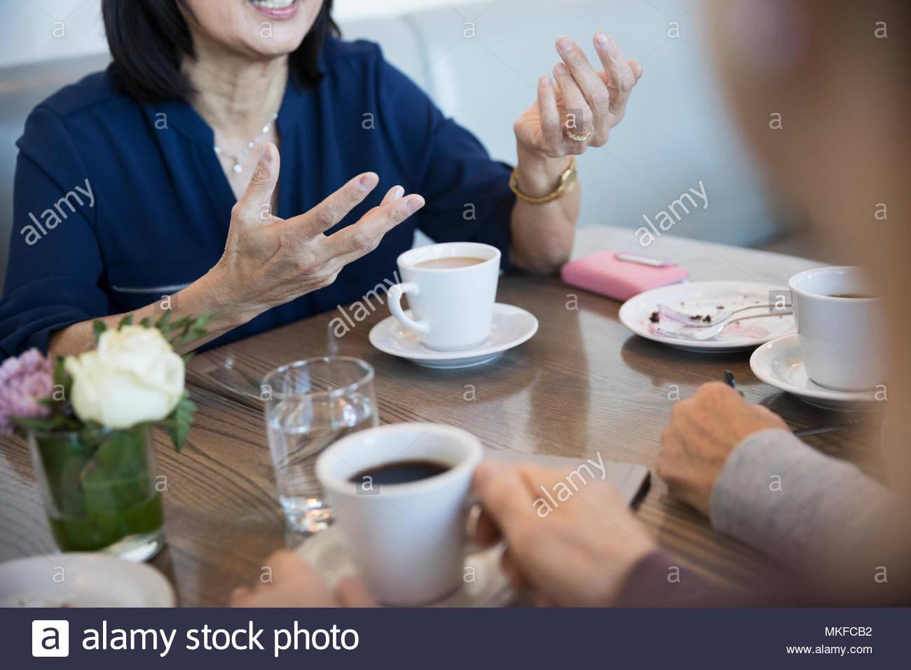 Ältere Frau im Gespräch mit Freunden, gestikulierte mit Händen in Cafe Stockbild