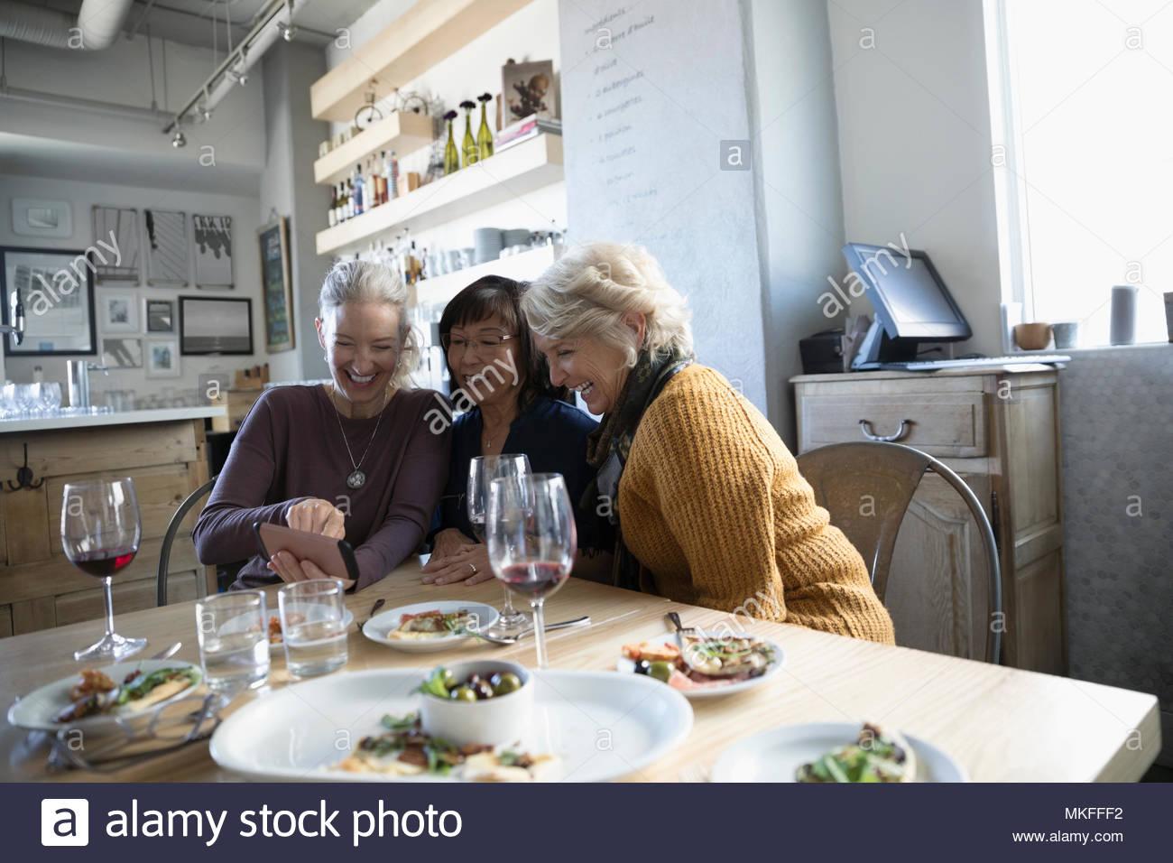 Active Senior Frauen Freunde mit Kamera Handy mit Vorspeisen und Rotwein im Cafe Stockbild