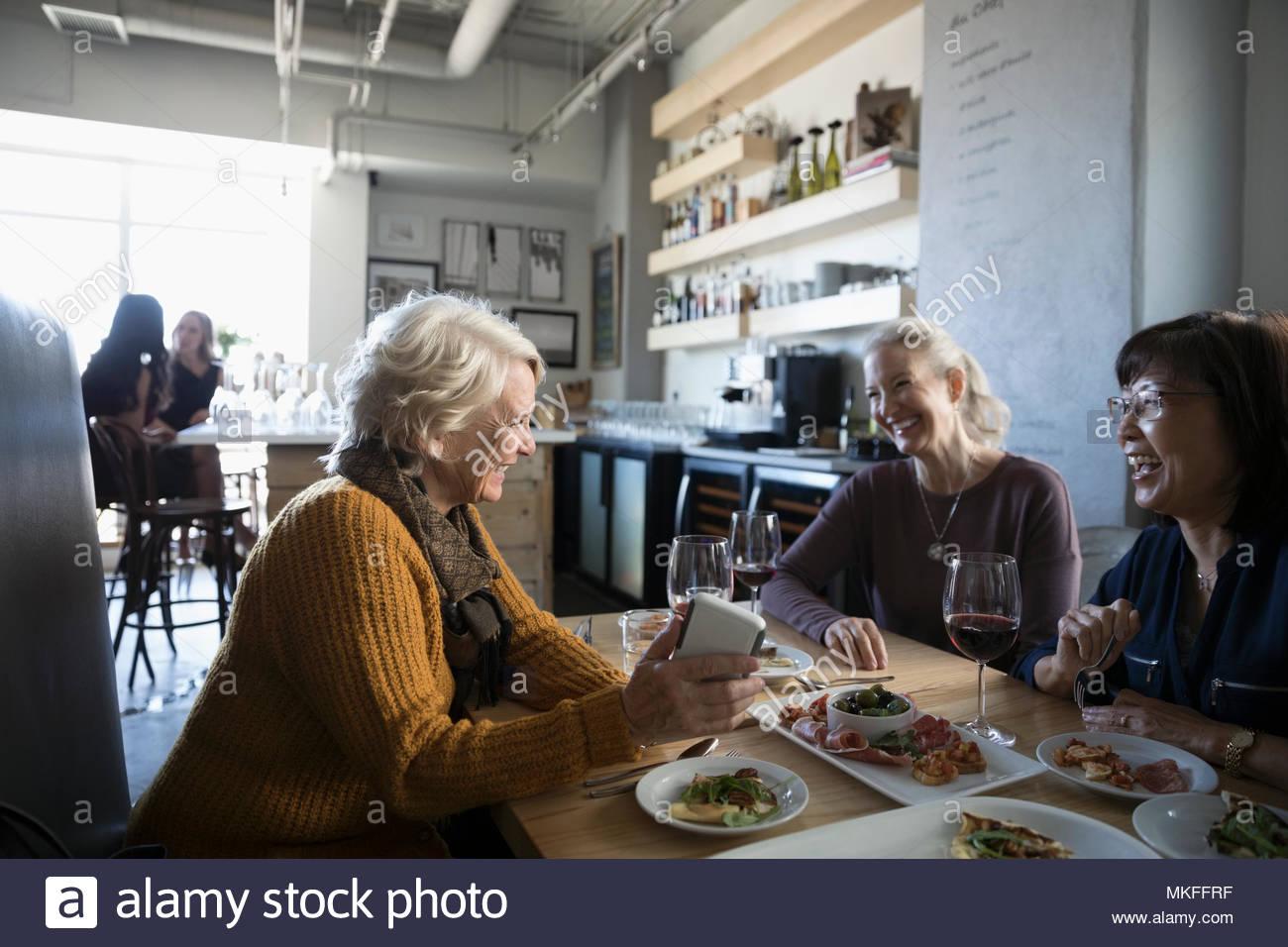 Active Senior Frauen Freunde mit smart phone Reden, Essen und Trinken Rotwein im Cafe Stockbild