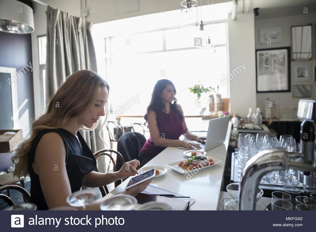 Unternehmerinnen arbeiten mit Laptop und einer Tablette in bar Stockbild