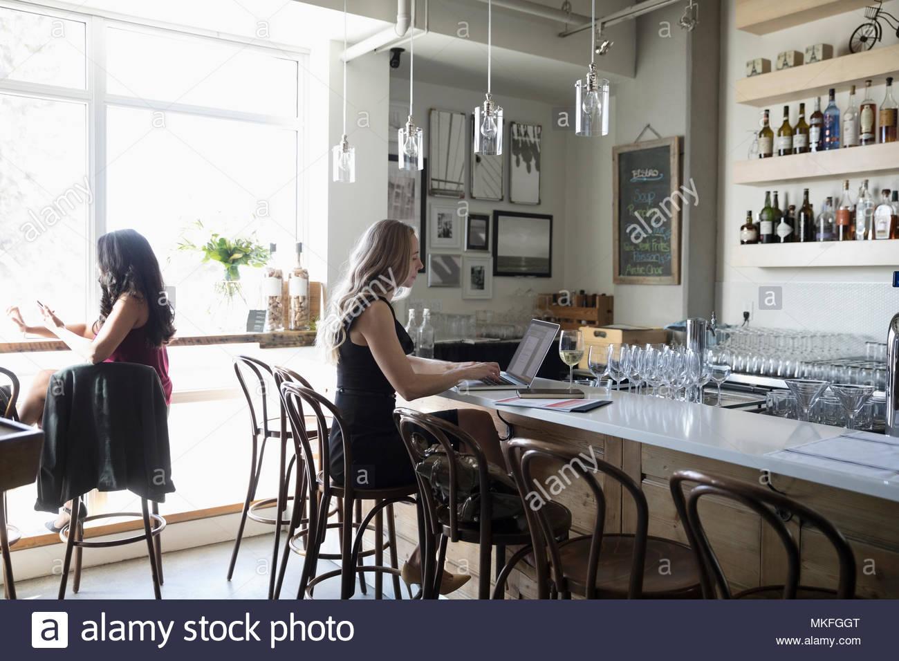Geschäftsfrau, Wein trinken und Arbeiten am Laptop in der Bar Stockbild