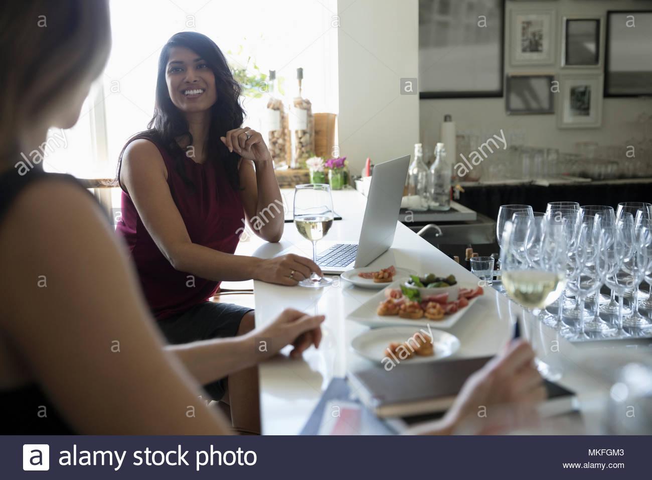 Unternehmerinnen arbeiten, genießen Wein und Häppchen in bar Stockbild