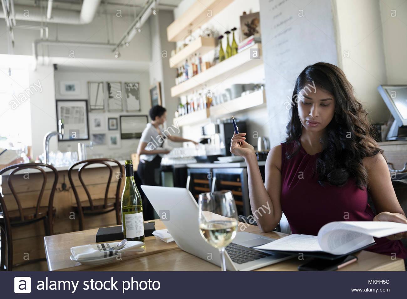 Geschäftsfrau, Wein trinken und Überprüfung von Unterlagen, am Laptop arbeiten im Cafe Stockfoto