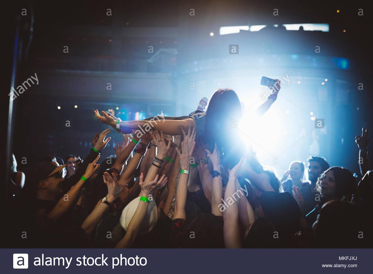 Frau mit Kamera Handy crowdsurfing auf Konzert in Nachtclub Stockbild