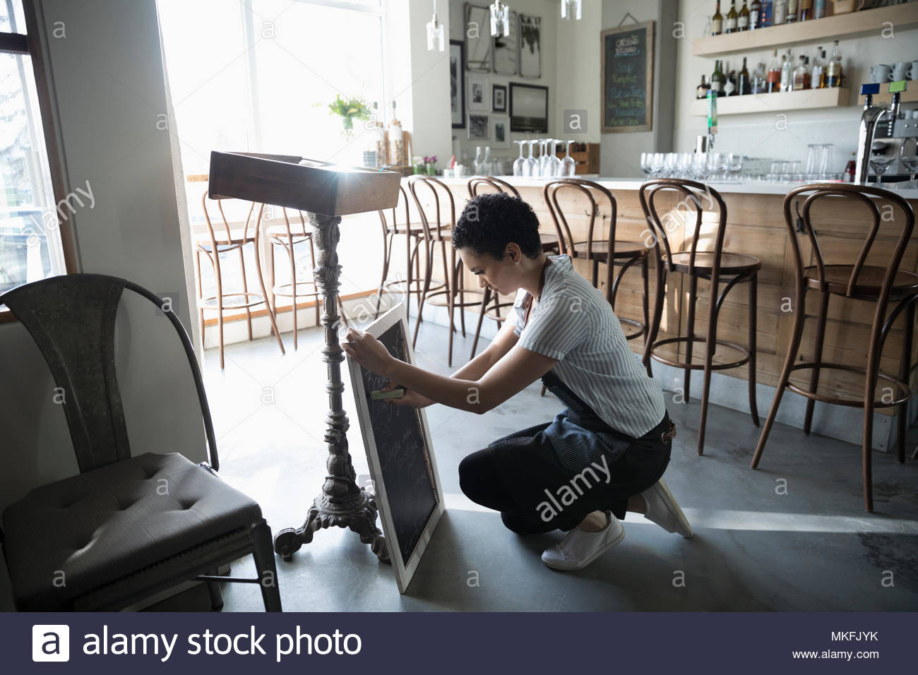 Junge Frau Kleinunternehmer Vorbereitung Menü auf Cafe Tafel Stockbild