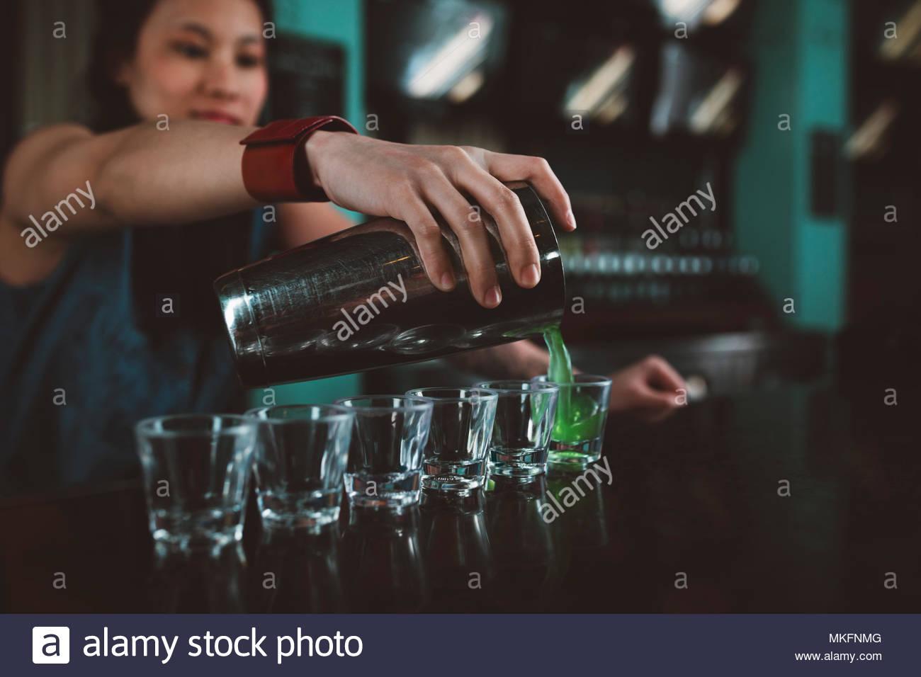 Junge weibliche tausendjährigen Barkeeper gießen Schüsse an der Bar Stockbild