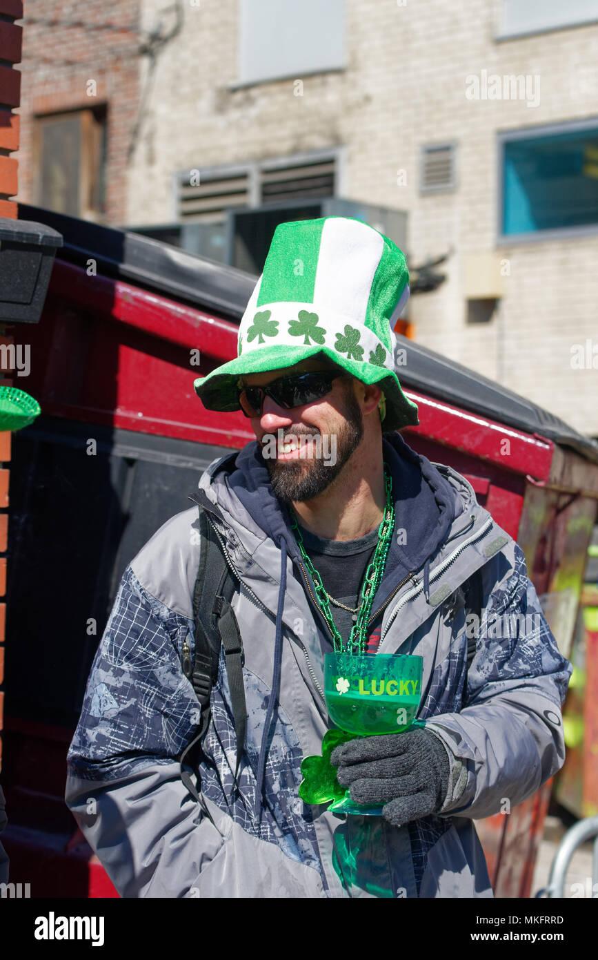 Ein Zuschauer bei der Montreal St. Patrick's Day Parade trägt einen grünen Hut und trinken Bier aus grünem Glas Stockbild
