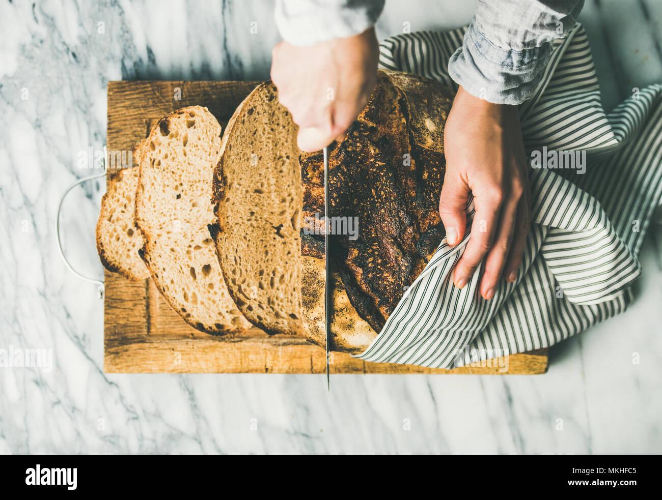 Weibliche Hände schneiden frisch gebackenem Sauerteigbrot in Stücke Stockbild