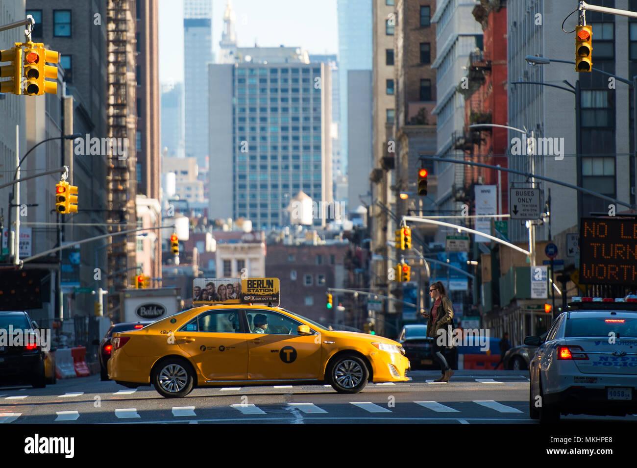 NEY YORK-USA - 28. Oktober 2017. Ein gelbes Taxi kreuzt ein Schnittpunkt zwischen den 42 Straße während des Sonnenuntergangs in Manhattan. Stockbild