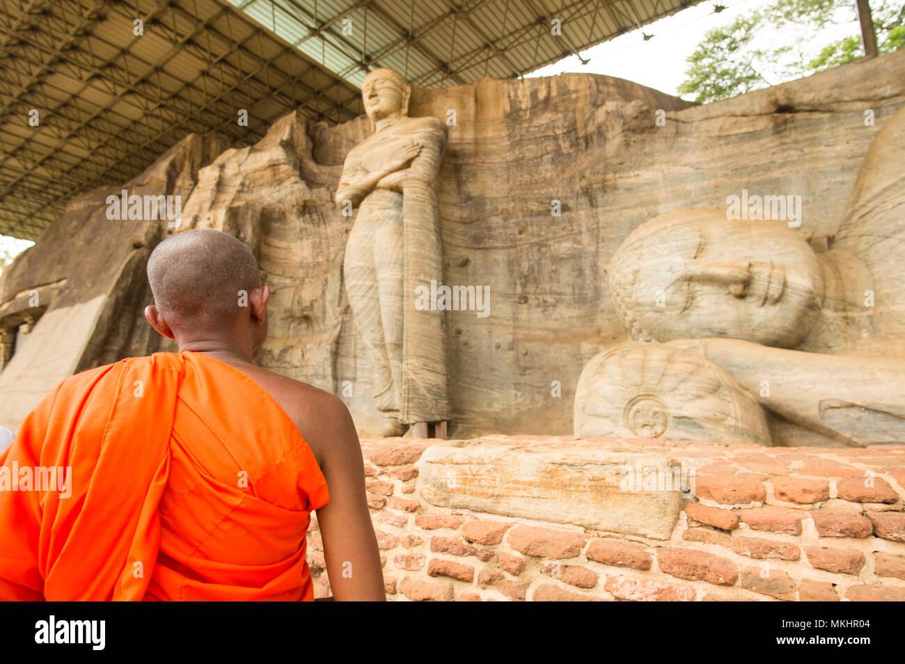 Ein Mönch ist zu Fuß vor der Statue des Liegenden Buddha und Mönch Ananda in das Gesicht von Granitfelsen der Gal Viharaya, Polonnaruwa, Sri Lanka. Stockfoto