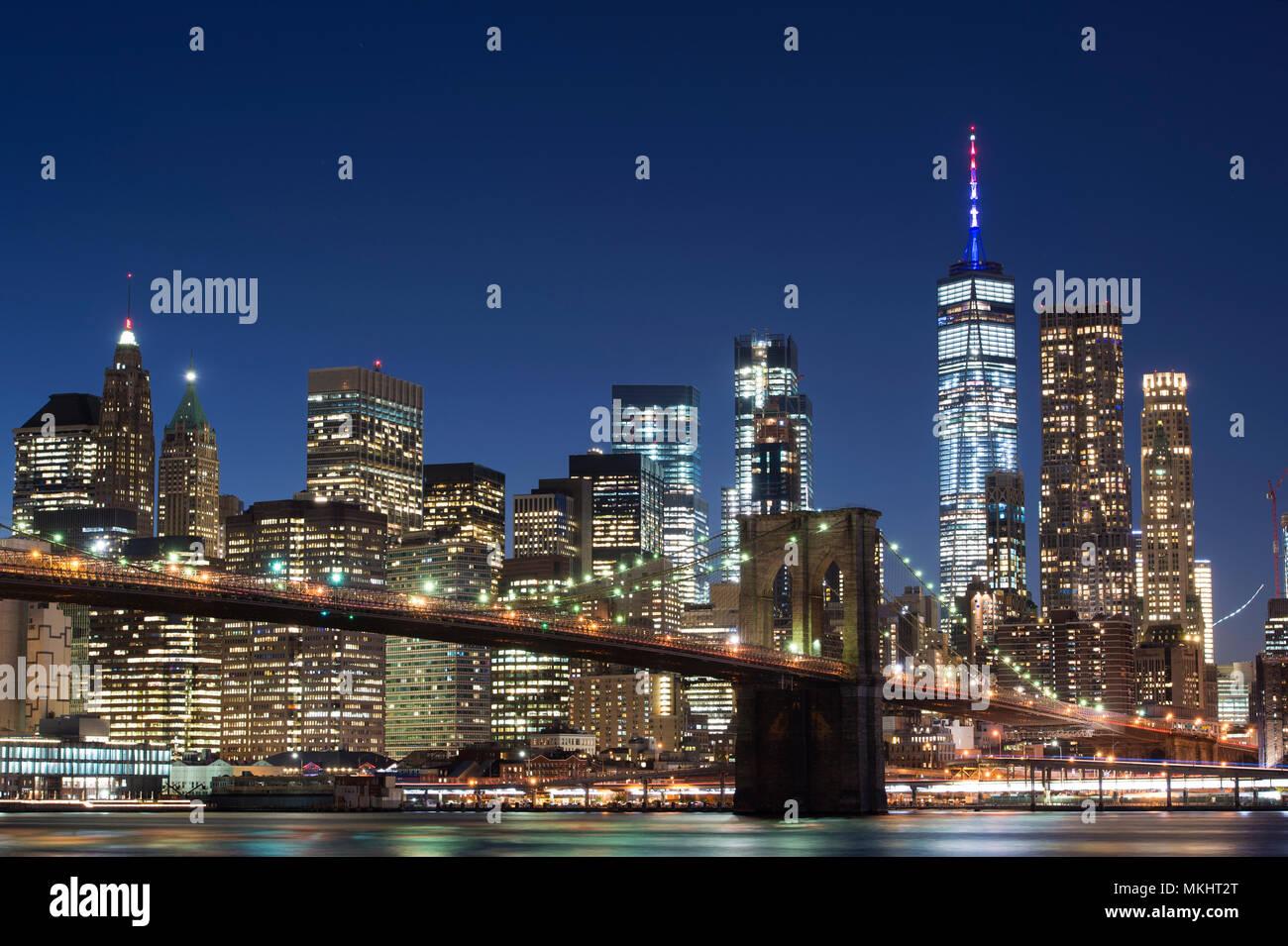 Brooklyn Bridge und die beleuchtete Skyline von Manhattan am Abend mit blauem Himmel und glatte Wasseroberfläche geschossen aus Brooklyn, New York, USA. Stockbild