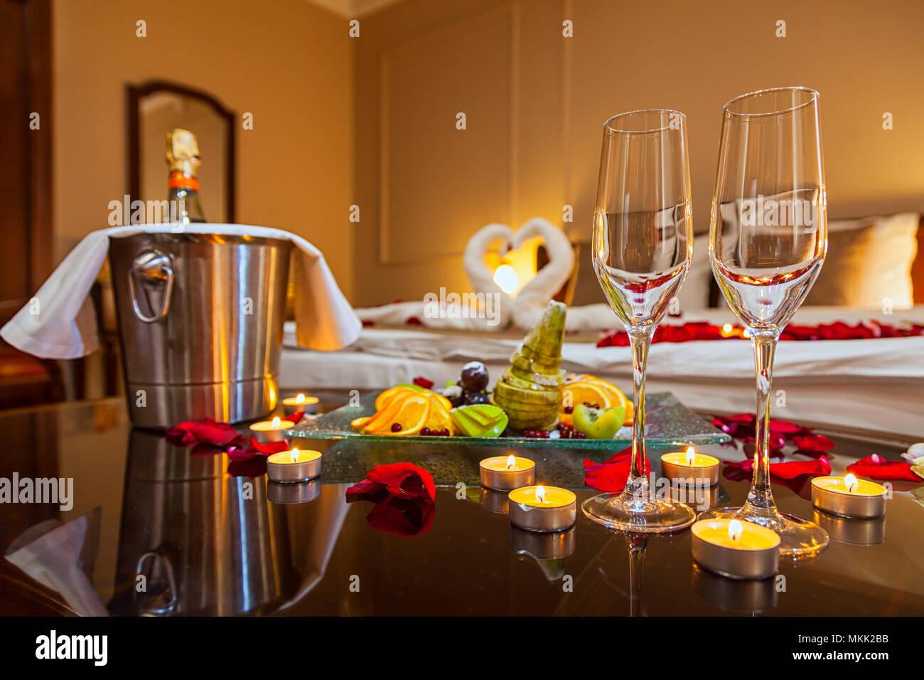 Hotel Zimmer Für Eine Hochzeitsreise: Eine Tabelle Mit Einem Obstteller Und  Kerzen, Im Hintergrund Ein Bett Mit Schwäne Aus Handtüchern Dekoriert Und  ...