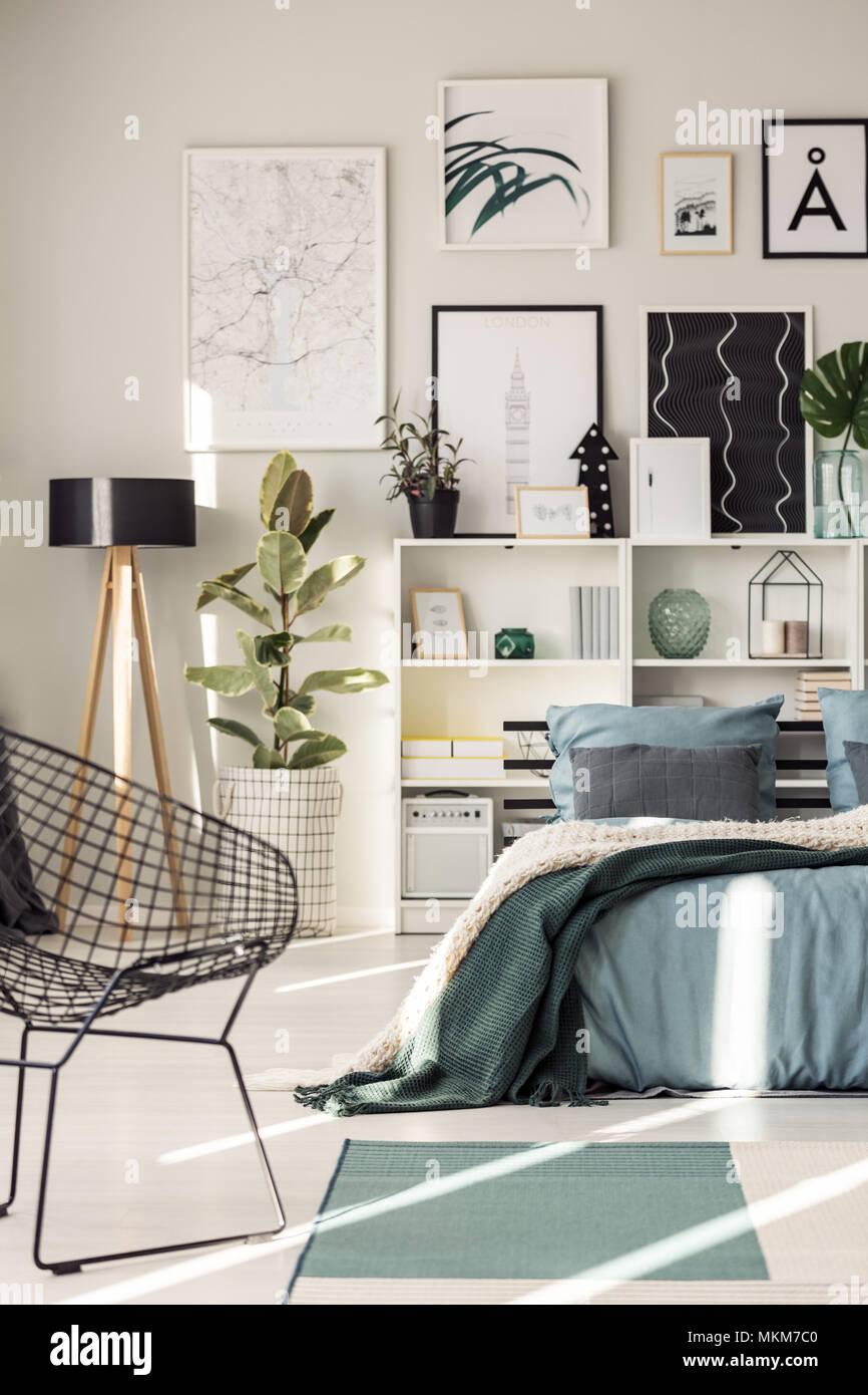 Attraktiv Sessel Neben Dem Bett Mit Grüner Decke Gegen Regale Und Poster An Der Wand,  In Modernen Schlafzimmer Innenraum