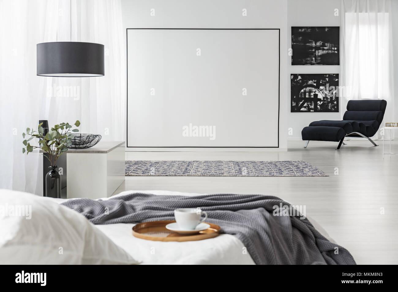 Graue Decke auf weißen Bett im Schlafzimmer Innenraum mit ...