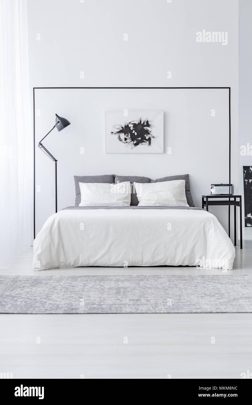 Schwarz Weiss Poster Uber Dem Bett Zwischen Tisch Und Lampe In Einfachen Schlafzimmer Innenraum Stockfotografie Alamy