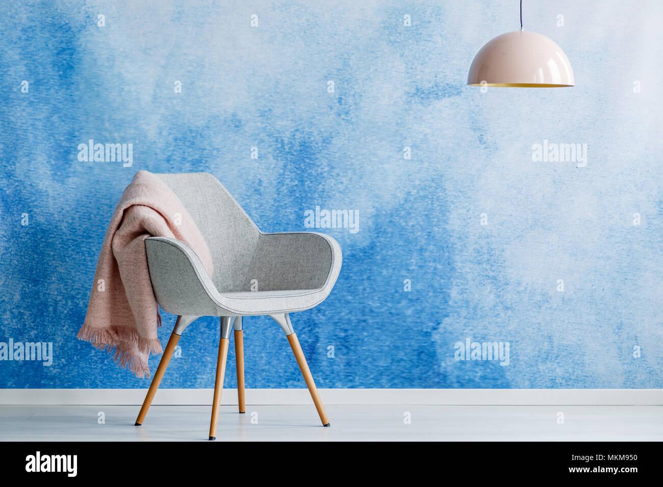 Rosa Decke auf grauen Sessel gegen blaue Wand in den leeren Wohnzimmer Innenraum mit Lampe und Kopie Raum Stockfoto