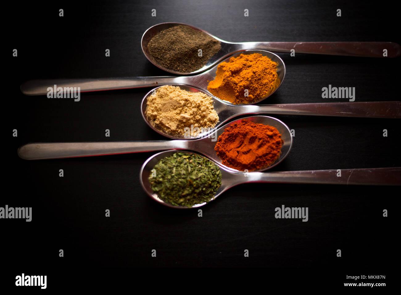 Gewürze farbige in Silber Löffel, auf einem schwarzen Holztisch gelegt. Pfeffer, Pfeffer, Salz, Basilikum, Senf Stockbild