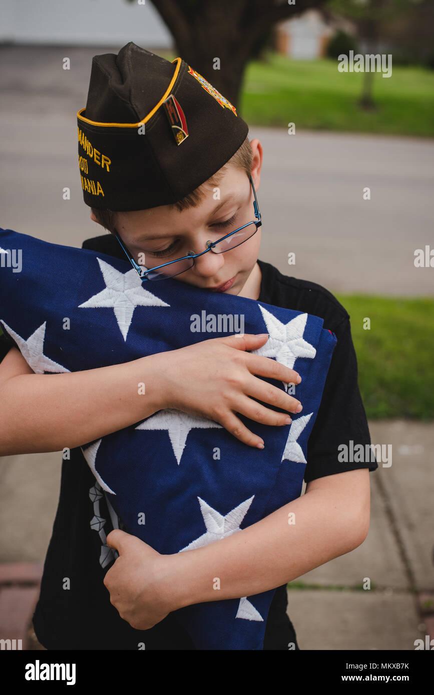 Ein Junge mit einem Gefalteten amerikanische Flagge. Stockbild
