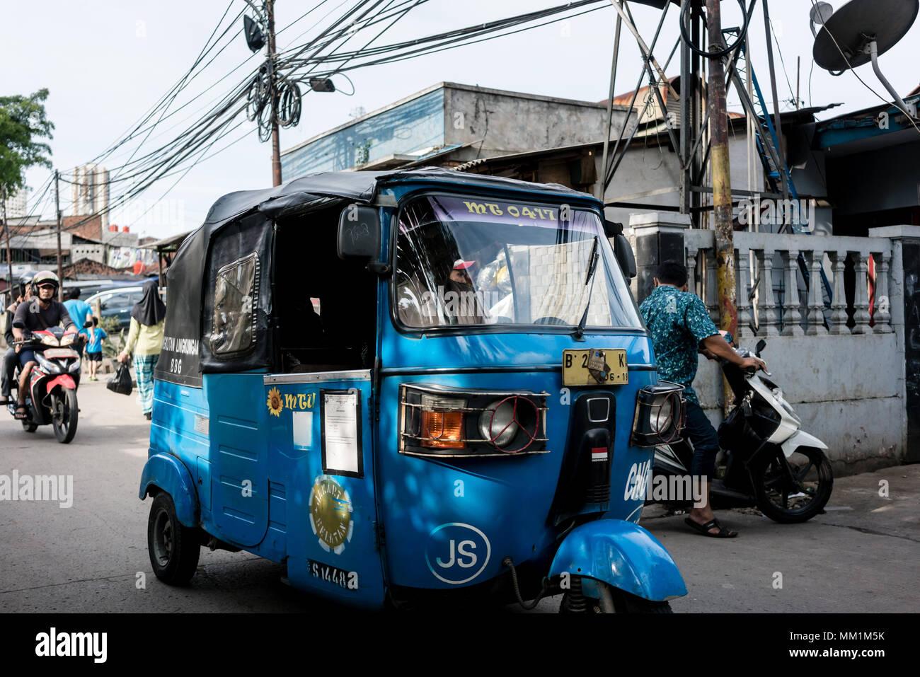 Blau Auto-rikscha auf einem engen und überfüllten Straße in einem armen Dorf in Indonesien Stockbild