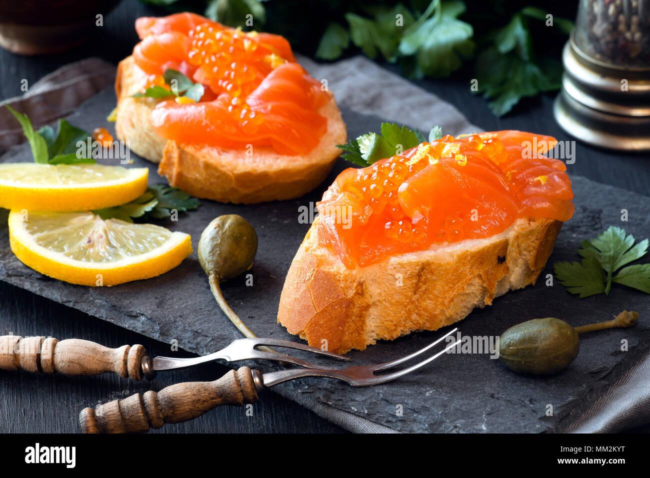 Canape Sandwiches mit geräuchertem Lachs und Kaviar oder samlon Eier auf schwarzem Schiefer mit Petersilie und Kapern Stockfoto