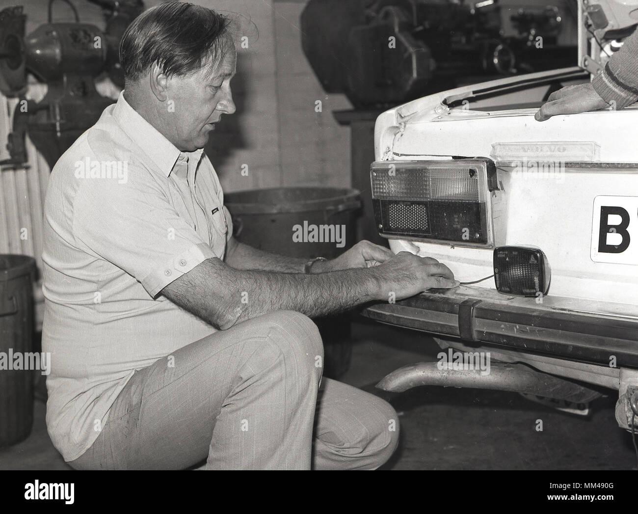 1970 s, historischen, ein Mann an einer Erwachsenenbildung klasse Auto Instandhaltung oder Wartung, Knieten während der Arbeit auf der Rückseite Lichter eines Volvo motorcar, England, UK. Stockbild
