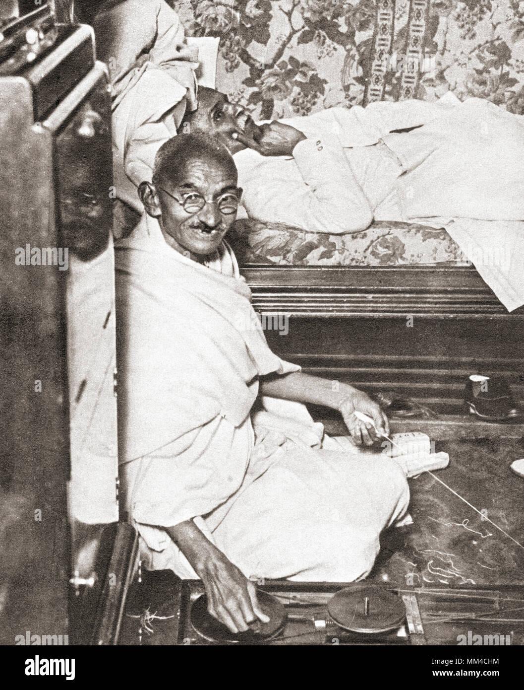 Mohandas Karamchand Gandhi, Mahatma Gandhi, 1869 - 1948. Die indische Aktivistin, Führer der indischen Unabhängigkeitsbewegung gegen die britische Herrschaft. Hier an der Konferenz am Runden Tisch, 1931 gesehen. Auf dem Fußboden neben ihm ist sein Spinnrad, ein Symbol von seinem Versuch, die indische Industrie auf Kosten der britischen Handel wieder zu beleben. Aus dem Festzug des Jahrhunderts, veröffentlicht 1934 Stockbild