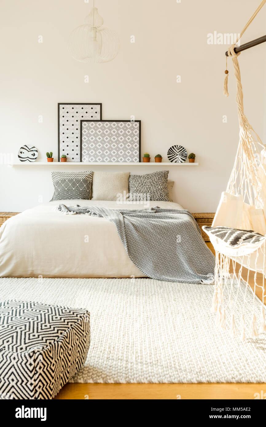 Gemusterten Kissen Auf Dem Bett Gegen Weisse Wand Mit Plakaten Auf Dem Regal In Scandi Schlafzimmer Innenraum Stockfotografie Alamy