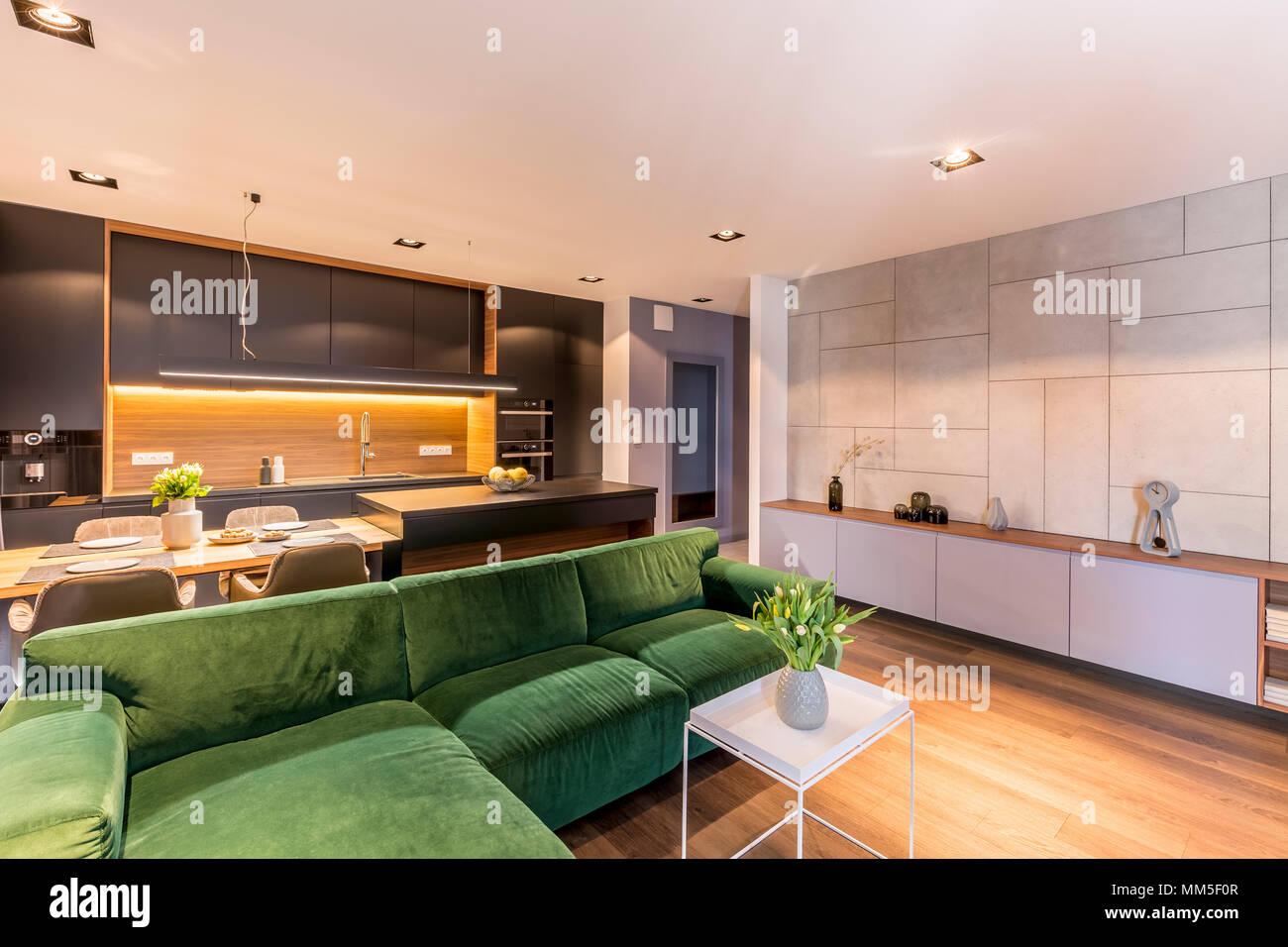 Grune Ecke Couch In Der Nahe Von Weissen Tisch Mit Blumen In Gemutliche Wohnung Interieur Mit Grauen Kuche Stockfotografie Alamy