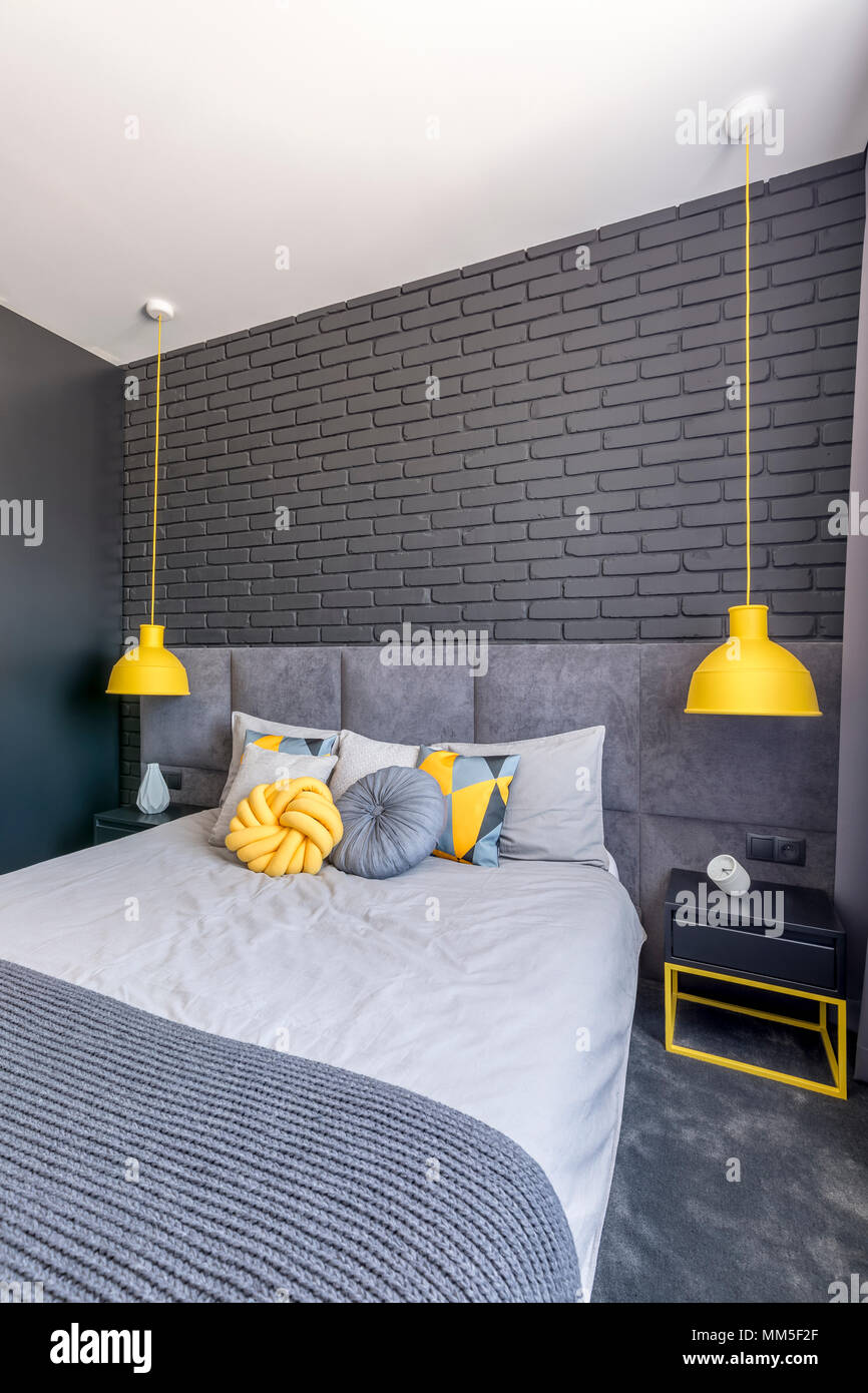 Grau Bett zwischen gelben Lampen in modernes Schlafzimmer Innenraum ...
