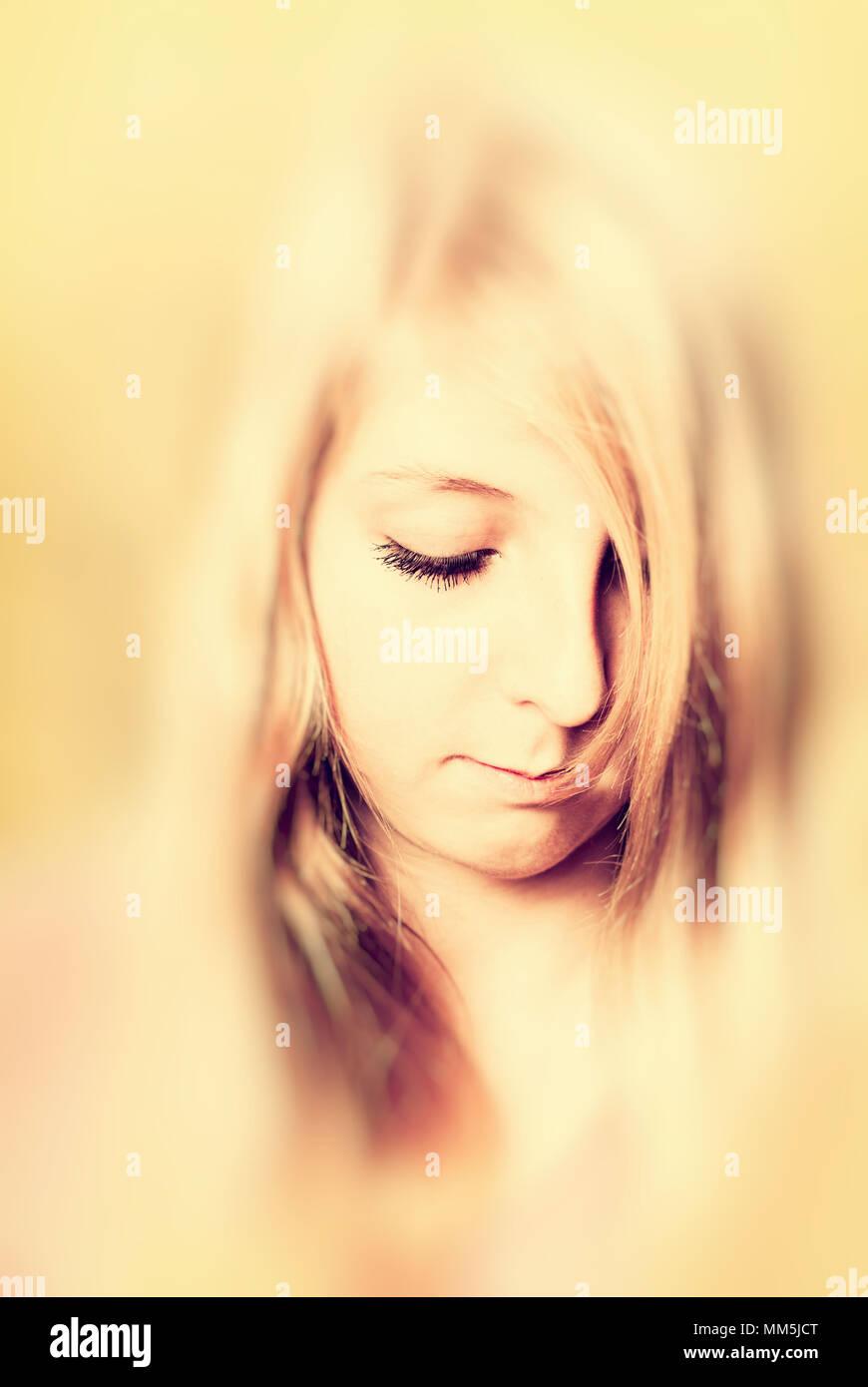 Blonde Mädchen mit langen Haaren und nachdenklicher Ausdruck und ätherisch mit Vignette Blur Stockbild