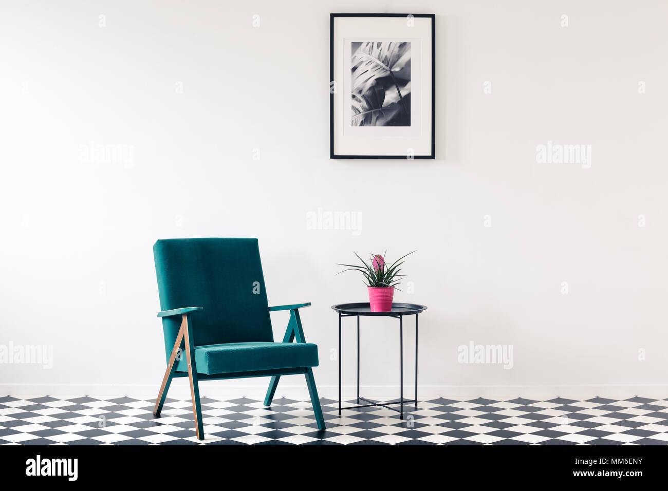 Rosa Blume auf dem Tisch neben einem türkis Sessel auf Schachbrett ...