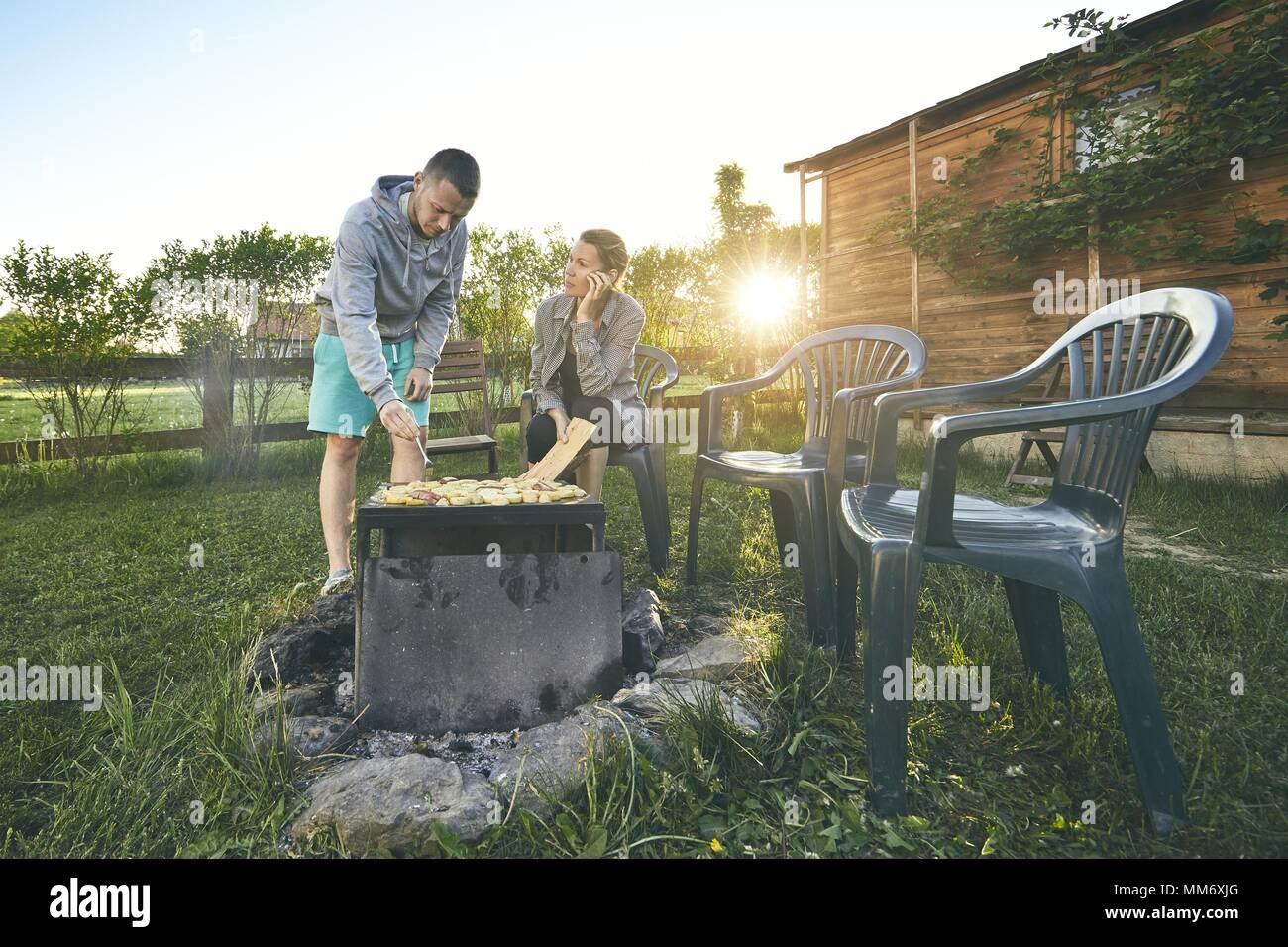 Im Sommer auf der Gartenterrasse. Junges Paar Grillen gegen Chalet am Sonnenuntergang. Stockbild