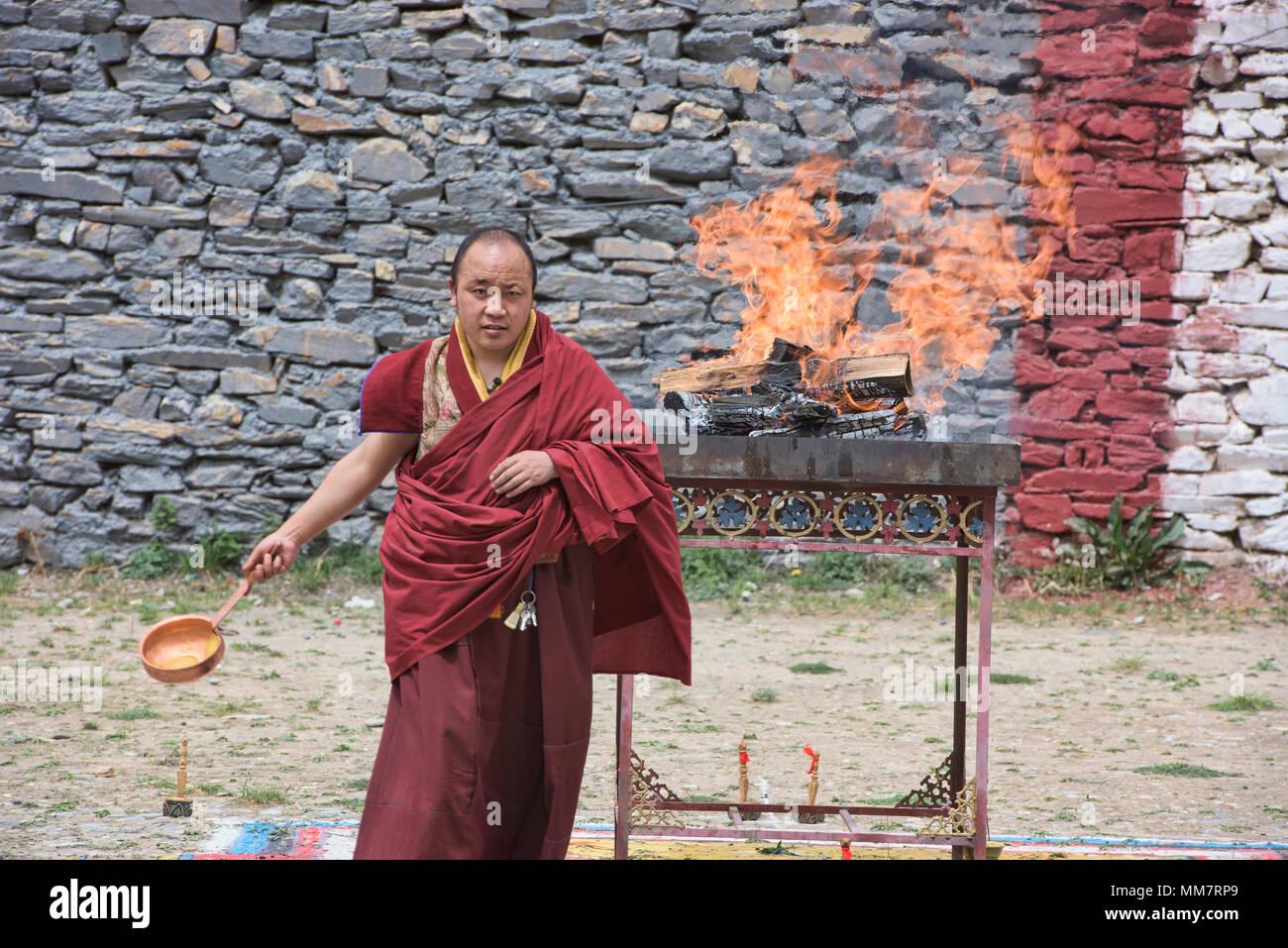Tibetischen Mönch legt yak Butter auf dem Feuer am Jinganqumo Reinigung Festival in Dege, Sichuan, China Stockbild