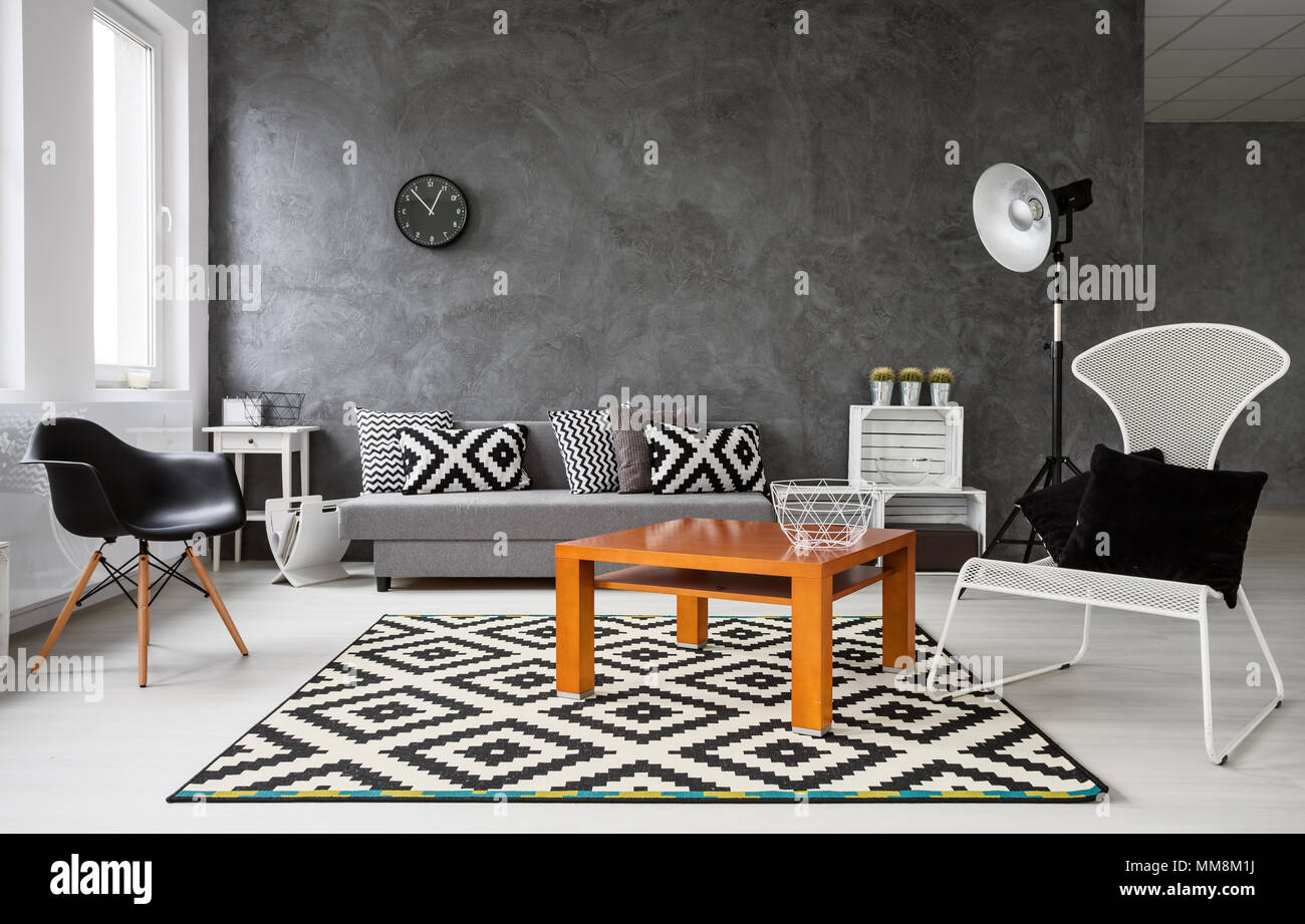 Geräumiges Wohnzimmer in Schwarz und Weiß gehalten. In der Mitte ...