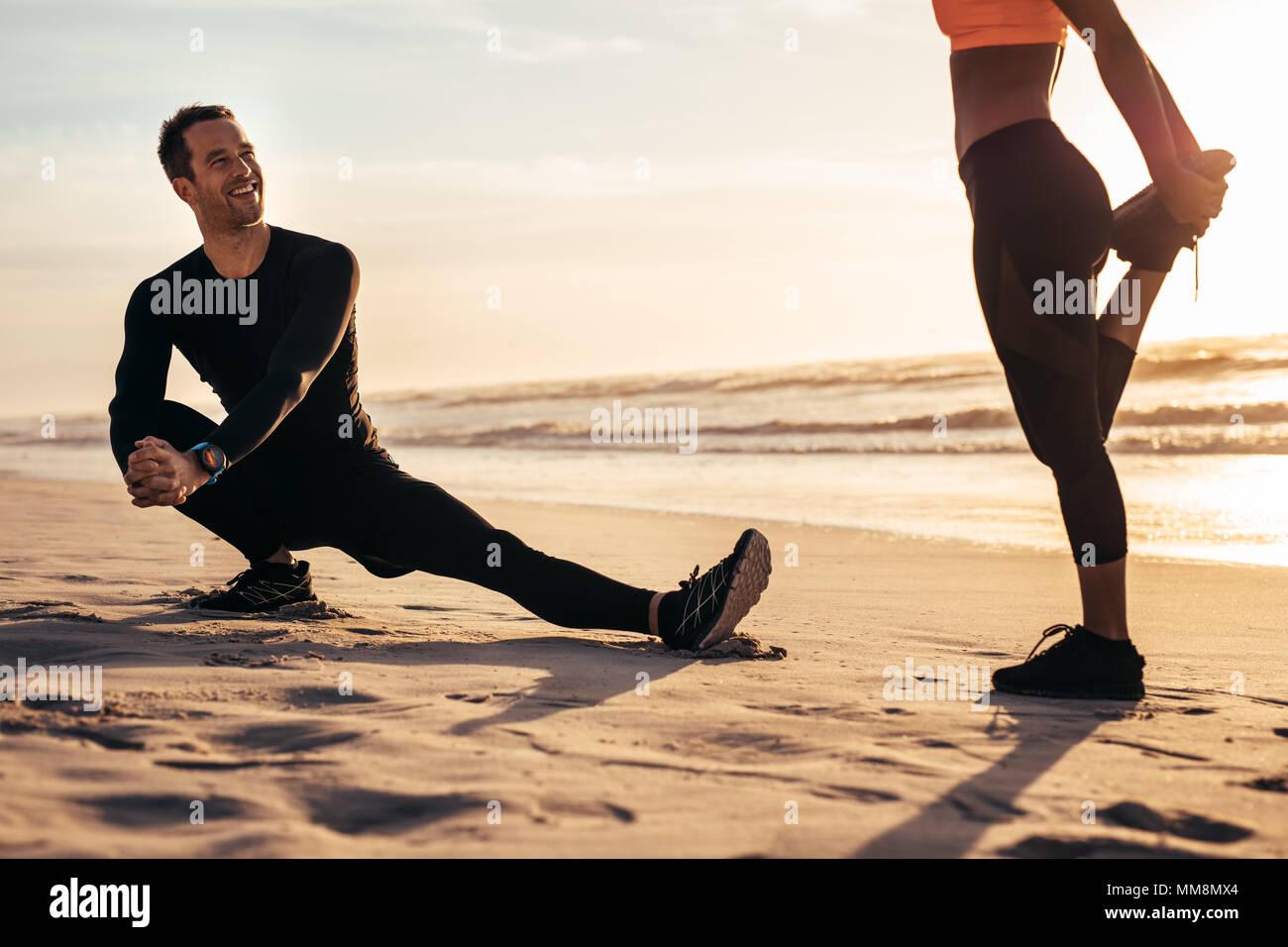 Jugendliche trainieren am Strand von Morgen. Runner dehnen und Aufwärmen entlang der Küste und in einen Chat. Stockbild