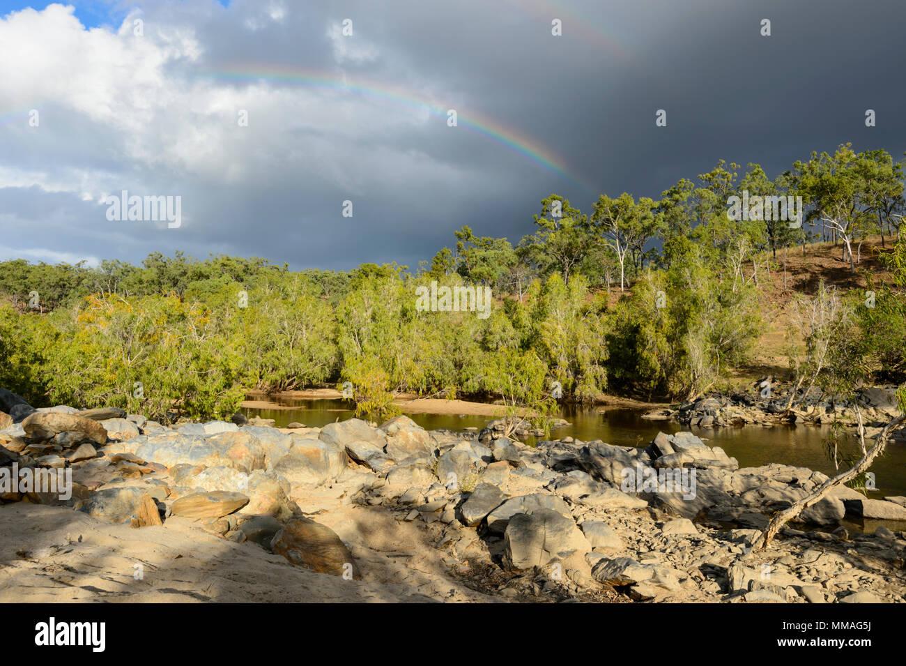 Schwarze Wolken und Regenbogen über Buschland in Palmer River Goldfield, Far North Queensland, FNQ, QLD, Australien Stockfoto