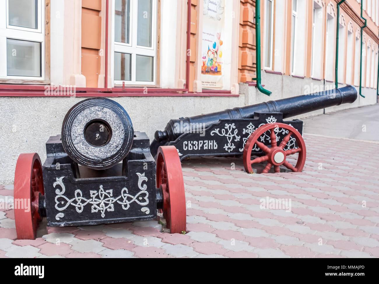 Syzran', Russland - August 16,2016: Zwei schwarze Kanonen mit roten Räder als Installation in der Nähe der Stadt lore Museum. Stockbild
