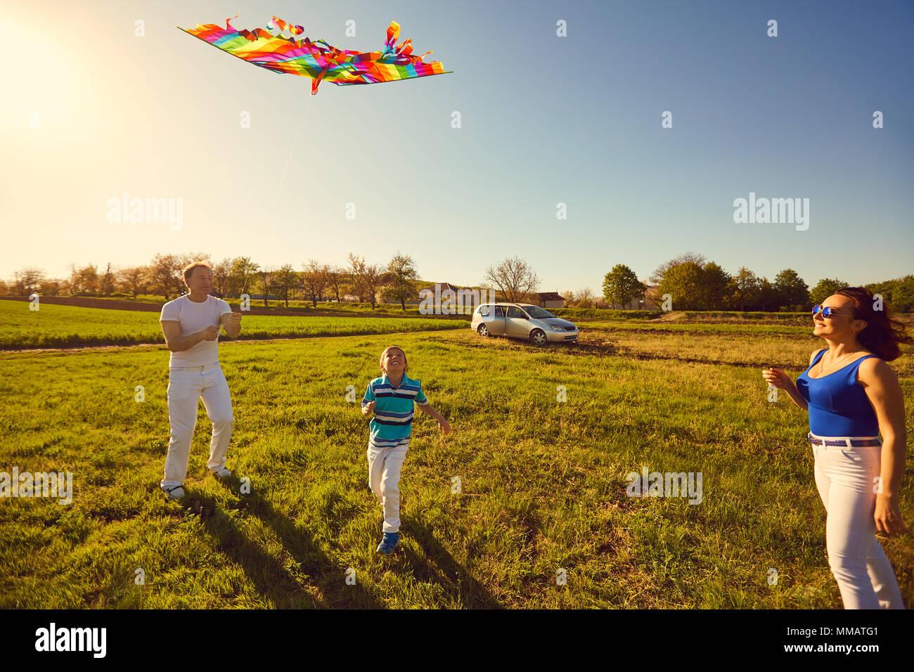 Glückliche Familie mit einem Drachen spielen im Feld in der Natur Stockfoto