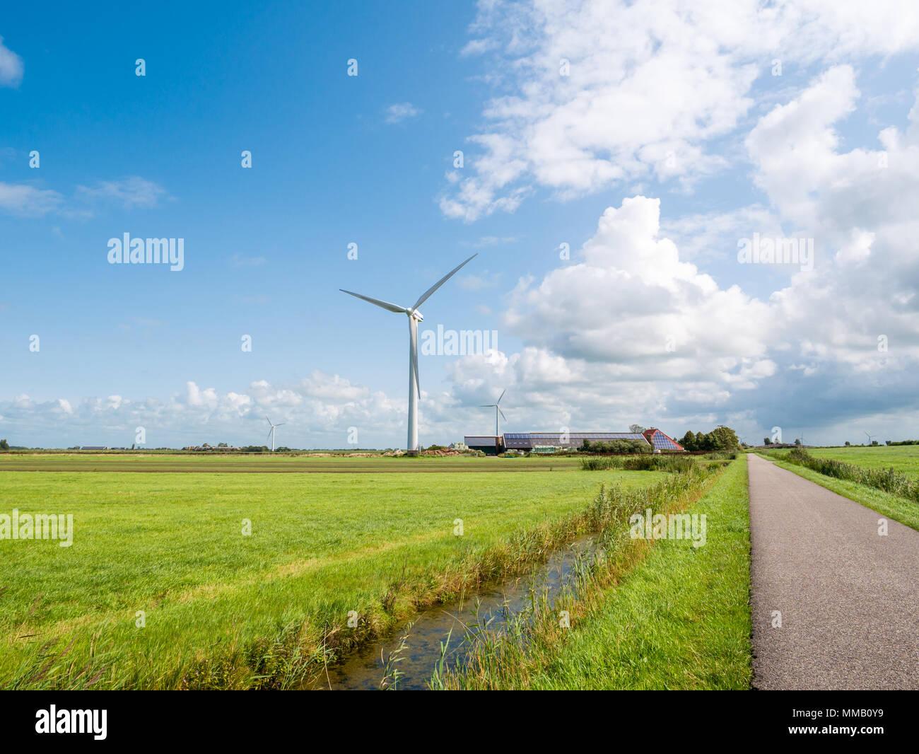 Bauernhof mit Solarzellen und Wind Generator im Polder in der Nähe von Makkum, Friesland, Niederlande Stockbild