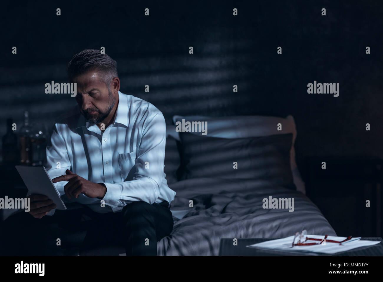 Erschöpft im mittleren Alter Mann sitzt auf einem Bett in einem Hotel Zimmer nachts und in einen Editor suchen während seiner Corporate Business Reise Stockbild