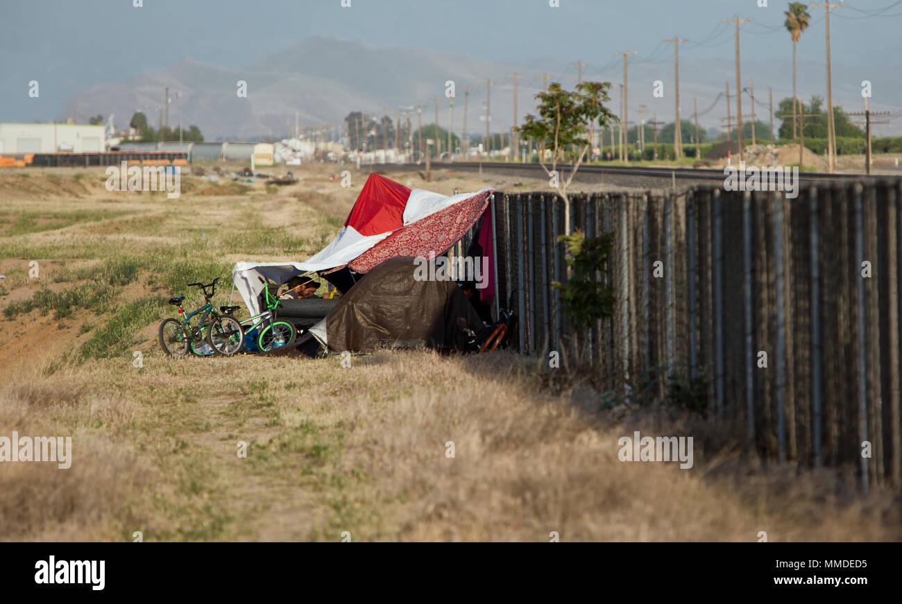Obdachlose Lager gegen Zyklon Zaun & Eisenbahnschienen. Stockbild