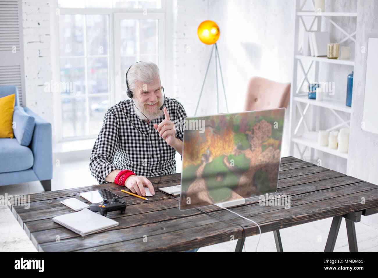 Upbeat älterer Mann mit Freunden chatten, während das Spiel Stockbild